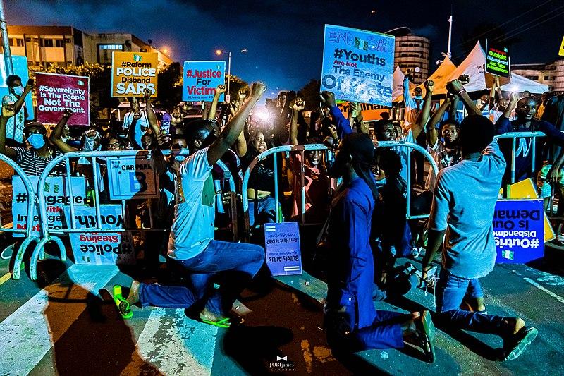 Trois hommes s'agenouillent devant une foule de manifestant·e·s brandissant des pancartes