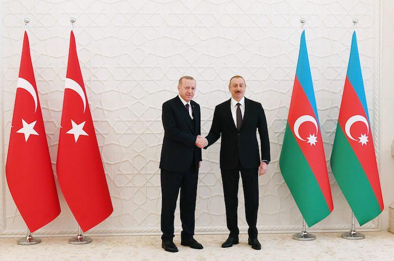 Une poignée de main entre le Président turque et le Président azerbaïdjanais entre les drapeaux des deux pays.