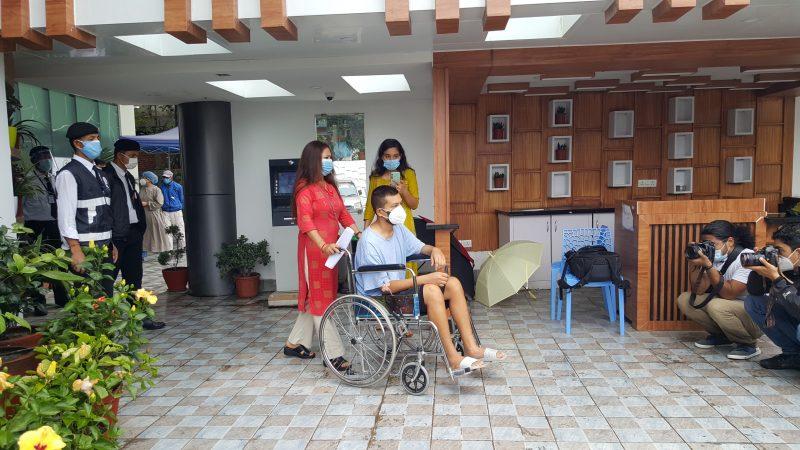 Iih se déplace en fauteuil roulant. Des journalistes le prennent en photo lors d'une conférence de presse.