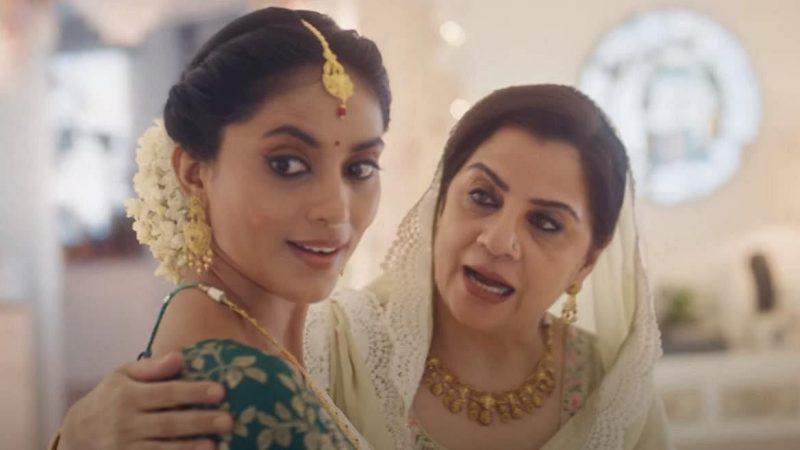 Une jeune femme portant des bijoux en or semble surprise, tandis que sa belle-mère la prend par l'épaule.