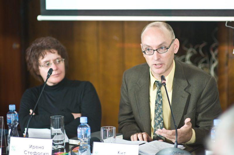 Keith Brown s'exprime au micro à la conférence de presse pour la promotion de son ouvrage, tandis que Irena Stefoska l'écoute attentivement.