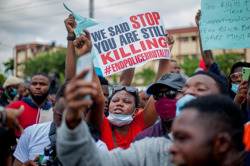 Une foule de manifestants brandissent des pancartes contre les violences policières à Lagos, au Nigeria.