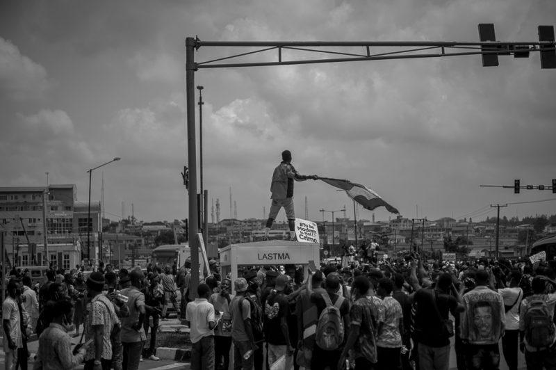 Une foule de manifestants occupent une rue. L'un d'eux est juché sur un promontoire et agite un drapeau.