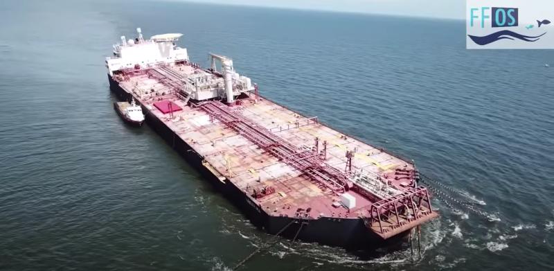 """L'image montre un gigantesque vaisseau localisé en pleine mer. Il apparaît amarré avec des chaînes le maintenant dans l'océan. La surface du navire est de couleur rose. La mer est calme. En haut, à droite de l'image, il y a le logo """" FFOS """", Fishermen and Friends of the Sea """", (Les Pêcheurs et les Amis de la mer)."""