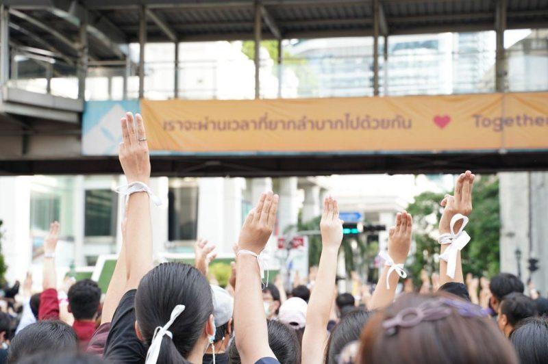 Des manifestations sont dans la rue, portent des rubans blancs au poignet et ont leurs 3 doigts en l'air.