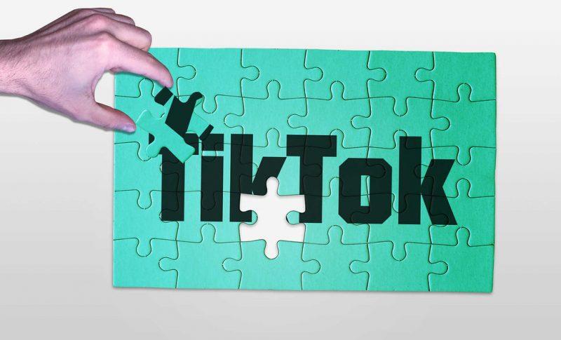 Une main fini un puzzle avec écrit Tiktok sur fond vert