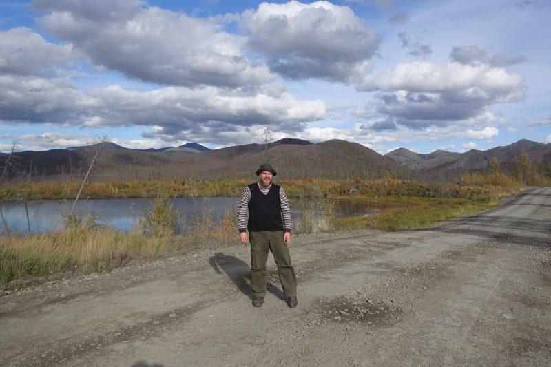 L'écrivain Ville Ropponen se tient debout devant un lac et un paysage vallonné, portant un pantalon large et un pull rayé.