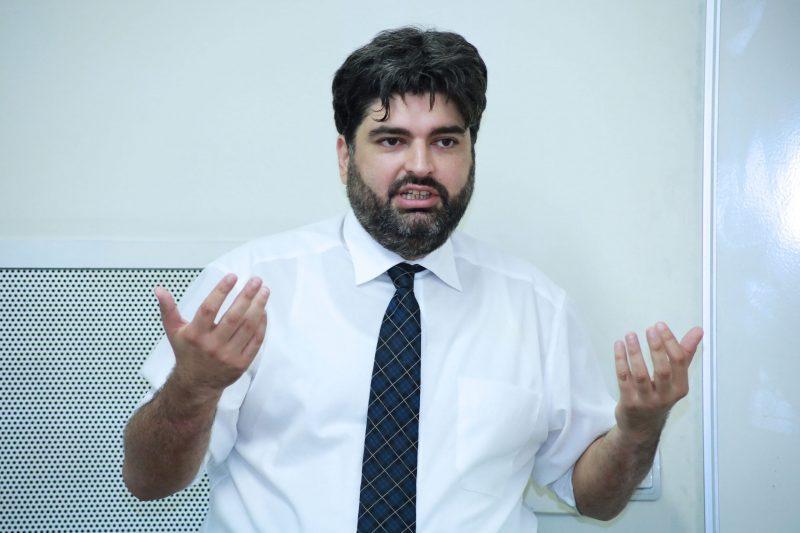 Le politicien et analyste arménien Mikayel Zolyan, en chemise et cravate. Ses bras sont levés au niveau des épaules, il semble en pleine explication.