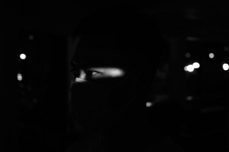L'image est en noir et blanc. On distingue un visage en gros plan. Seuls les yeux, de type asiatique, sont visibles car éclairés. Ils sont ouverts et regardent sur le côté. Tout autour, il y a quelques points lumineux flous.