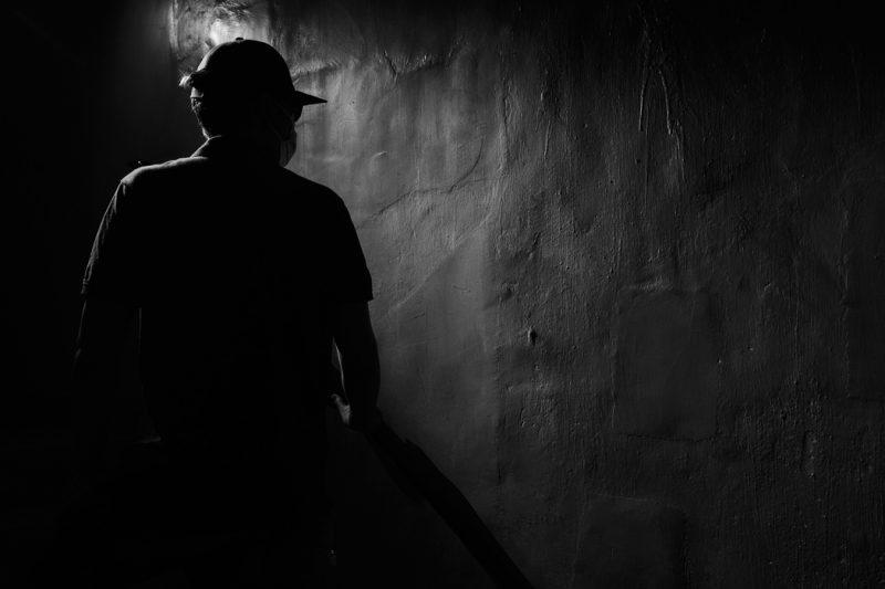 On distingue un homme de dos dans le noir, marchant près d'un mur. Il porte une casquette et un masque de protection faciale. Il se tient légèrement de profil, et regarde vers le mur. Une partie de son ombre est projetée sur ce mur nu. L'image est en noir et blanc.