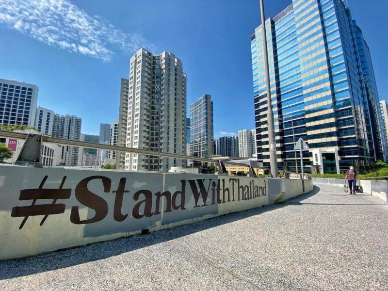 Message #StandWithThailand sur pont piéton avec grattes ciel en fond. Photographie.