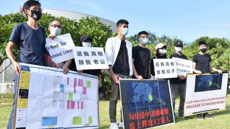 8 activistes protestant contre l'arrestation des 12 jeunes. Ils portent tous un masque de protection faciale et tiennent des banderoles et panneaux.