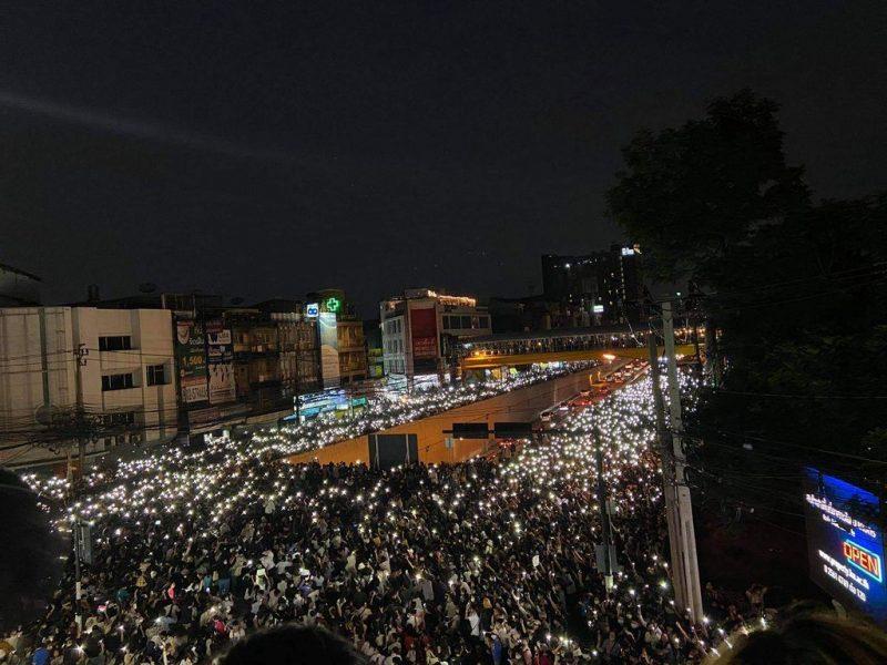 L'image montre un large rassemblement compact de personnes dans la rue, sur un pont. La grande majorité tient leur portable allumé, en l'air. On distingue des habitations et des bâtiments tout autour. L'image est prise de nuit et en hauteur.