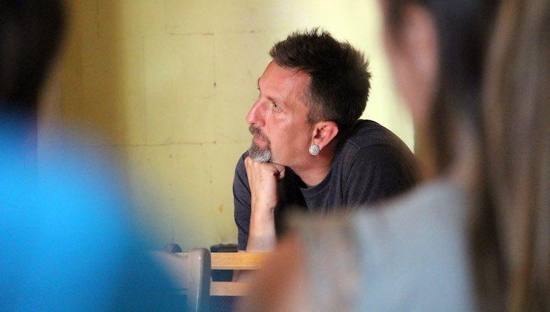 Valts Ernštreits est assis, l'air pensif, le menton soutenu par une main. Il porte une boucle d'oreille ronde et a une barbe poivre et sel.