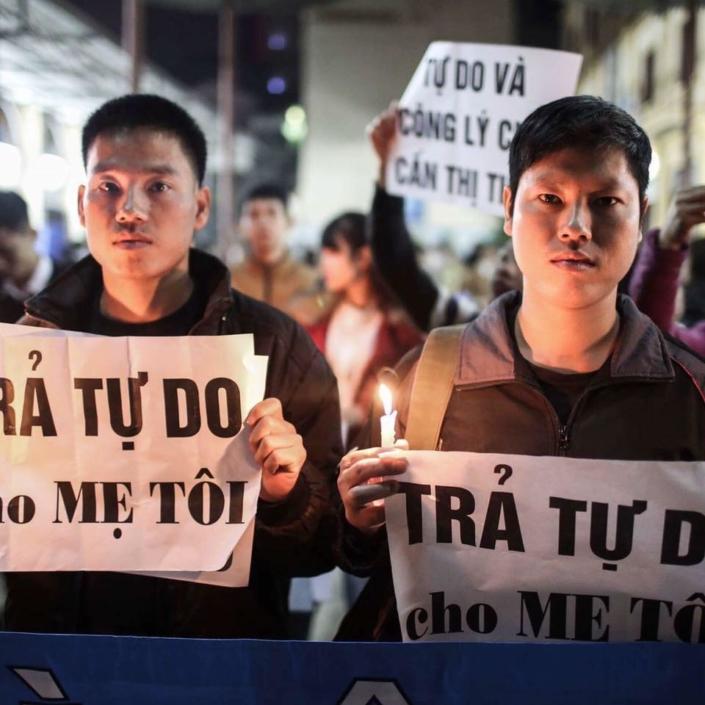 Trinh Ba Tu and son frère Trinh Ba Phuong se tiennent au milieu d'une foule, posant face caméra avec leurs pancartes en papier.