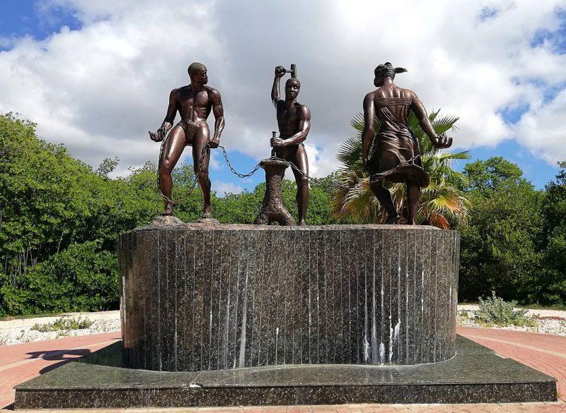 Statue de Tula en train de libérer deux personnes de leurs chaînes en frappant dessus à l'aide d'un marteau. Les trois figures sont situées sur un promontoire en marbre.