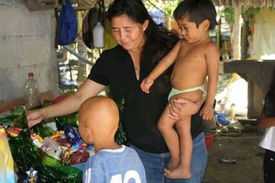 Une femme tient un jeune enfant dans un bras et montre des objets à un enfant malade. L'arrière-plan suggère des conditions de vie insalubres et financièrement difficiles.