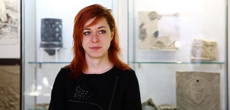 Portrait de la commissaire d'exposition Lejla Bečar, une femme d'âge moyen aux cheveux teints en orange. Elle se tient devant des vitrines du Musée national.