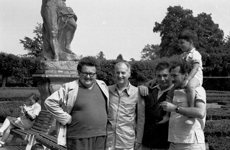 Quatre hommes souriant et posant dans un jardin public devant une statue. L'un porte un enfant sur ses epaules.