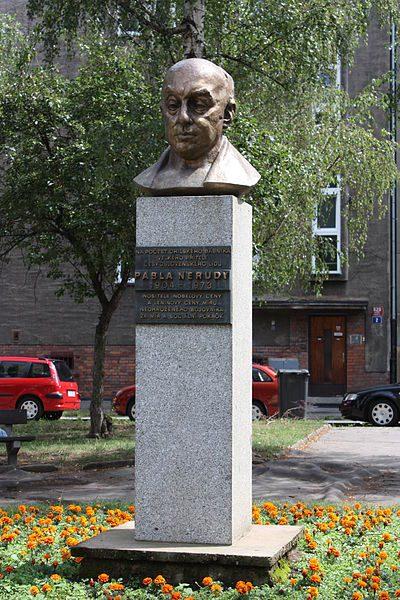 Photo citadine d'un buste aux allures de bronze sur socle de granite dans un parterre d'oeillets jaunes. Sous le buste, une plaque explique qu'il s'agit de Pablo Neruda.