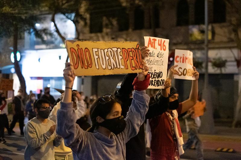 """Jeunes manifestants portant des masques hygiéniques dans la rue, la nuit. On peut voir 3 banderoles dont une montre le message: """"dis-le fortement Pérou"""""""