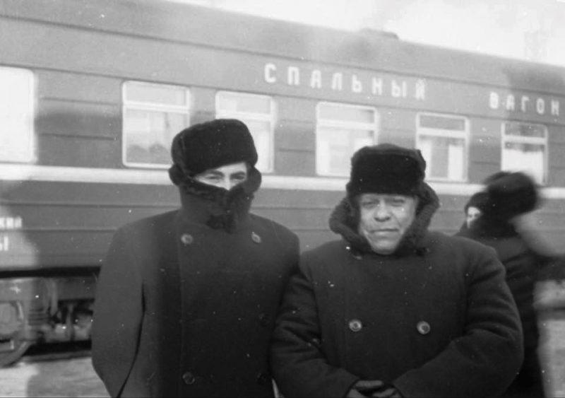 Deux hommes emmitouflés dans des manteaux à hauts cols de fourrure posent devant un train.