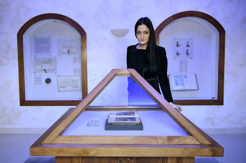 Lea Maestro, une jeune femme brune aux cheveux longs, se tient derrière un présentoir protégé par une vitre. On y voit un livre enluminé, la Haggada de Sarajevo.