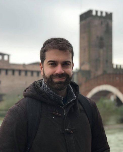 Photo de l'universitaire Zourek, jeune homme barbu et souriant dans un manteau d'hiver. Il pose devant une forteresse et un pont de briques.