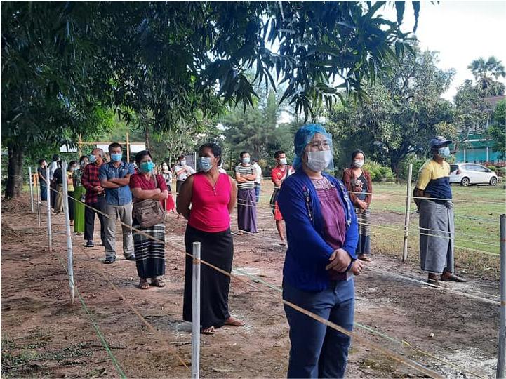 Des électrices et électeurs font la queue devant un bureau de vote au Myanmar, en se tenant à environ 1 m de distance. Tout le monde porte un masque de protection faciale.