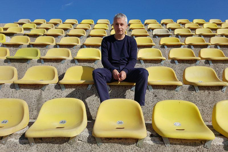 Le journaliste Nikola Gelevski, assis seul sur des gradins jaunes.