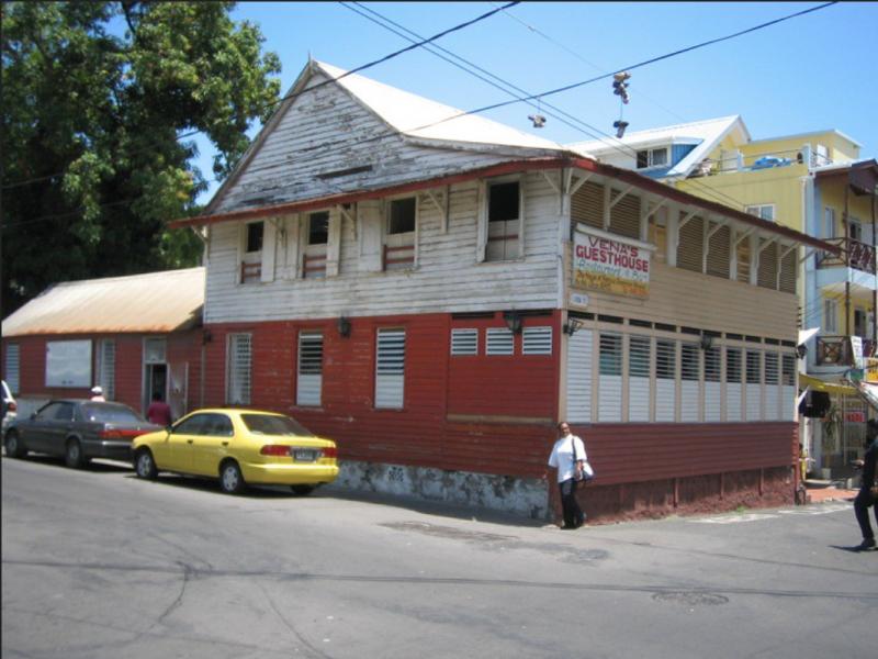 La maison d'enfance de Jean Rhys avant sa démolition. Une imposante maison en bois à deux étages, peinte en rouge et blanc.