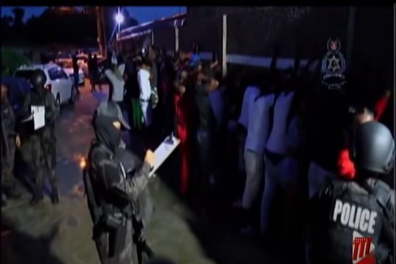 Photo floue où l'on voit la police en uniforme noir en train de fouiller des personnes au sortir d'une fête.