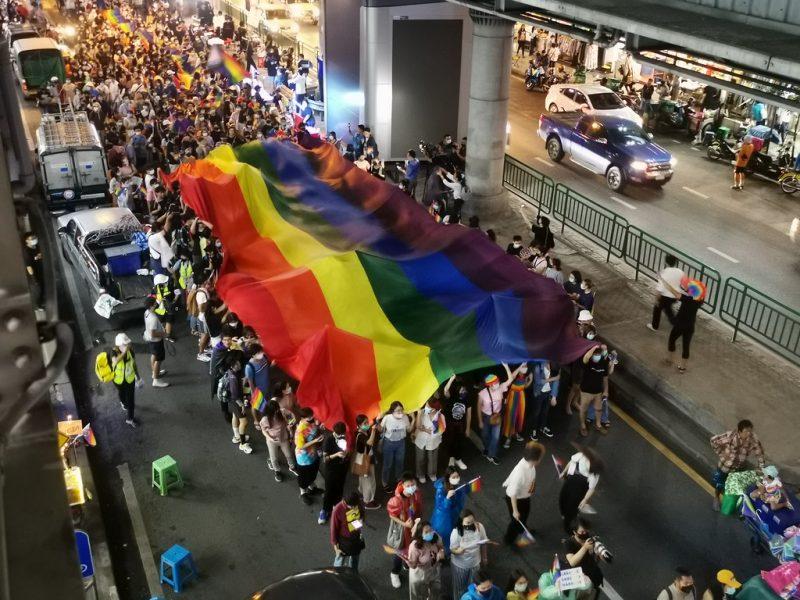 Des manifestants marchent dans la rue, tout en portant au dessus de leur tête le drapeau représentant la communauté LGBTQ+