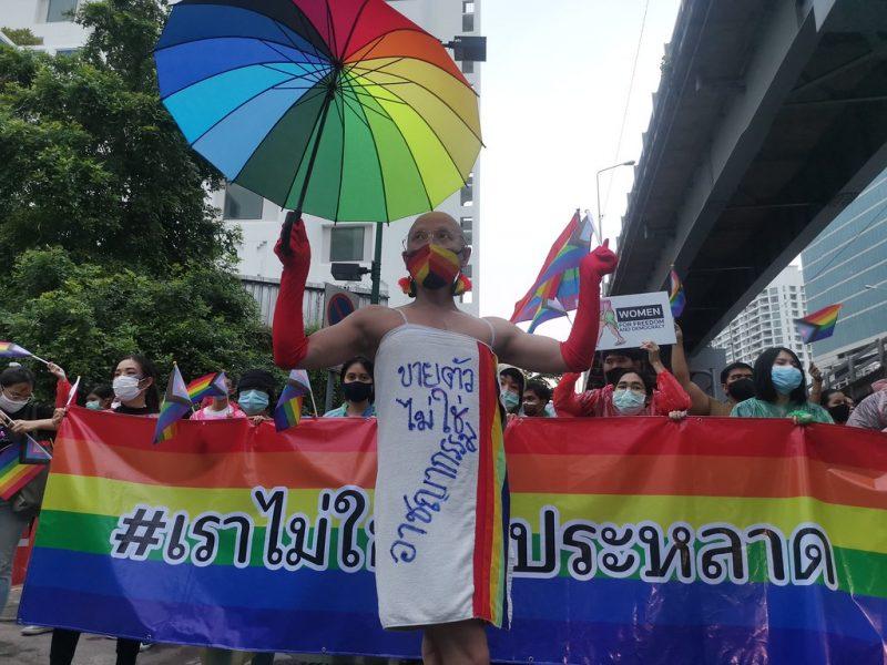 Au premier plan, un homme porte une serviette avec un message en thaïlandais écrit dessus, et tient un parapluie arc-en-ciel. Au second plan, des personnes tiennent un drapeau arc-en-ciel géant avec écrit un message en thaïlandais.