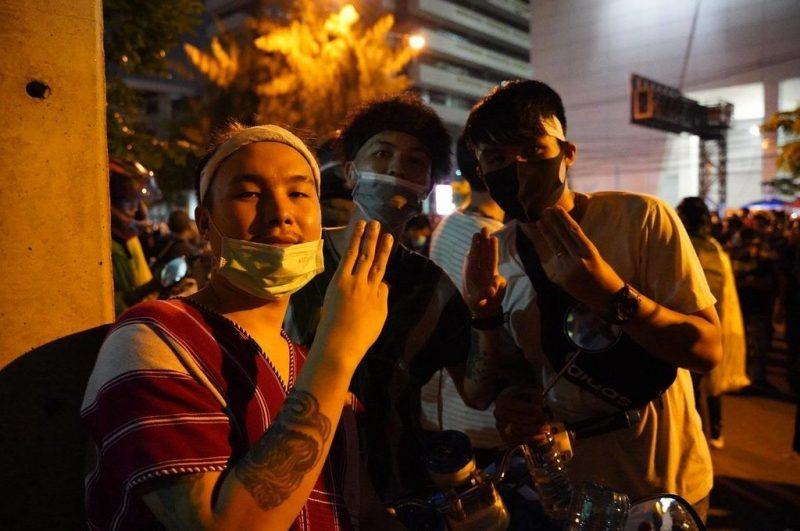 Trois jeunes manifestants font le salut à trois doigts dans une rue de Bangkokg. Tous portent des masques de protection faciale.