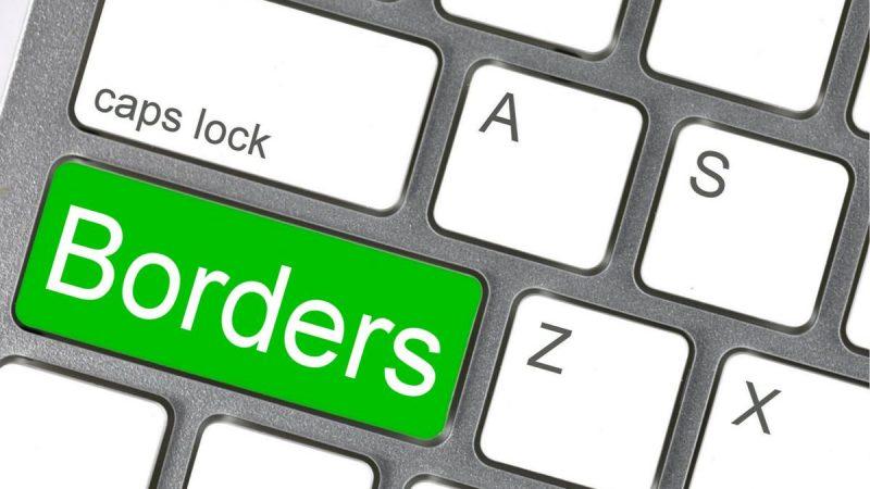 L'image montre en gros plan et de biais, une partie d'un clavier d'ordinateur. La touche « shift » a été remplacé par le terme « BORDERS » (frontières), en vert.