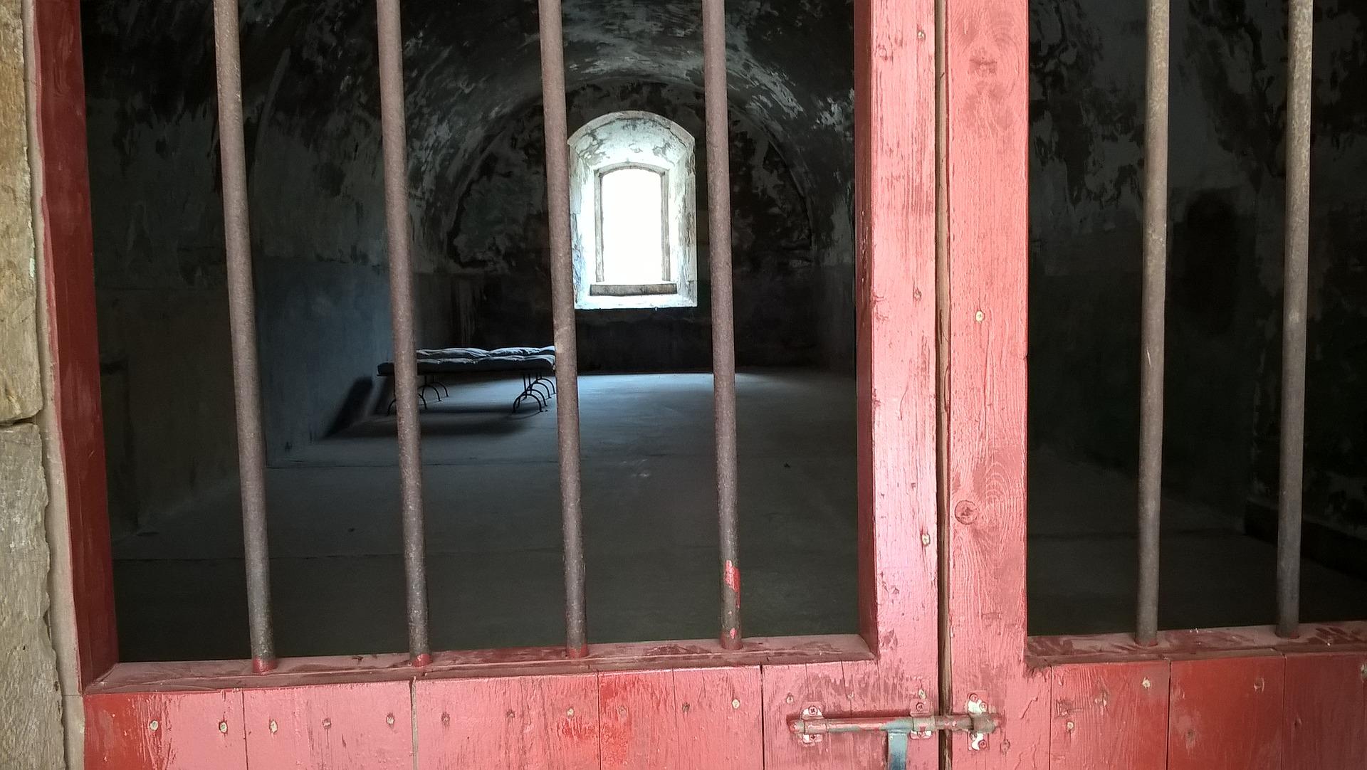 Une cellule de prison vue à travers les barreaux. Elle est vide, hormis un lit de fortune.