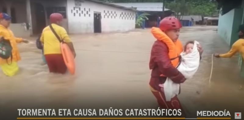 Une rue dans laquelle l'eau est montée jusqu'à la moitié des maisons. On peut voir 3 hommes avec de l'eau jusqu'au dessus des genoux. L'un tient dans ses bras un bébé emmailloté.