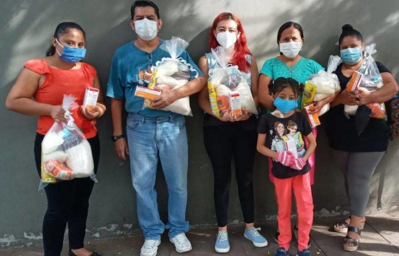 Cind adultes et une petite fille portant des masuqes posent les bras chargés compléments alimentaires et vitamines