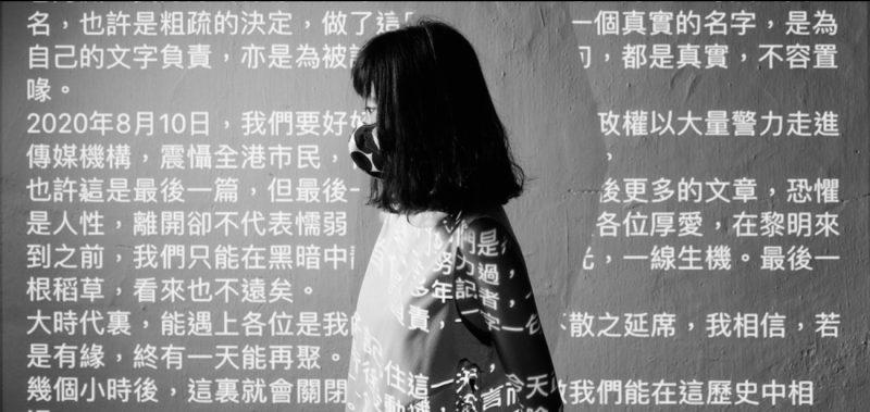 On distingue une jeune femme de profil avec un masque de protection faciale. Elle porte des lunettes et a des cheveux bruns mi longs. Elle se tient près d'un mur sur lequel est projeté un texte en caractères chinois. L'ombre de son corps apparaît sur le mur et cache une partie du texte. L'image est en noir et blanc.
