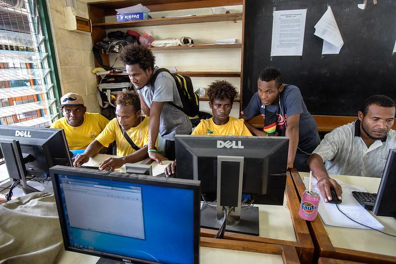 Un groupe d'étudiants travaille devant des ordinateurs de bureau dans une salle assez exigue. Certains tapent au clavier tandis que d'autres observent ou donnent des conseils.