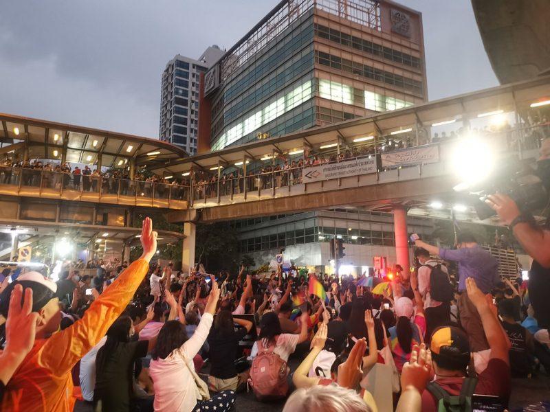 Des personnes se trouvent devant un bâtiment. Elles ont le bras levé avec seulement 3 doigts levés.