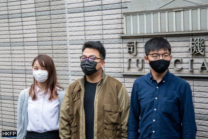 Plan moyen de 3 jeunes personnes, d'origine asiatique. Il y a deux jeunes hommes et une jeune femme. Les 2 hommes portent des lunettes et un masque noir de protection faciale. Celui du milieu est vêtu d'une veste beige marron claire et d'un t-shirt noir. Le 2ème homme porte une chemise bleue. La jeune femme, aux cheveux bruns clairs, est vêtu d'un chemisier blanc et d'un gilet bleu clair. Elle porte un masque de protection faciale blanc. Ils se tiennent devant un bâtiment judiciaire, avec une inscription en chinois et en anglais, de couleur grise. La photographie est prise de jour et à l'extérieur. Le logo HKFP apparaît en bas à gauche.