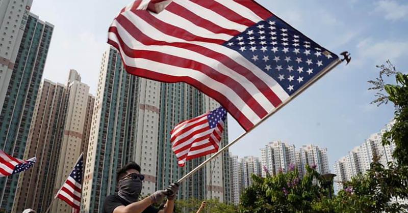 Un homme manifeste en brandissant un drapeau américain, qui occupe une bonne partie de l'image. Le visage du manifestant est quasi couvert par un foulard noir. Il porte des lunettes et un t-shirt de couleur noire et des gants. On distingue plusieurs drapeaux et de nombreux buildings, tout autour.