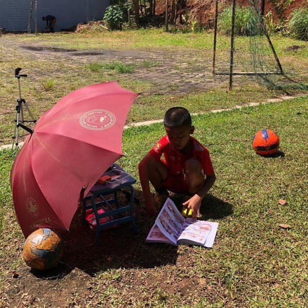 Ghazy lit un livre, accroupi dans l'herbe, abrité par un parasol rouge. Près de lui, un trépied pour caméra et deux ballons de football.