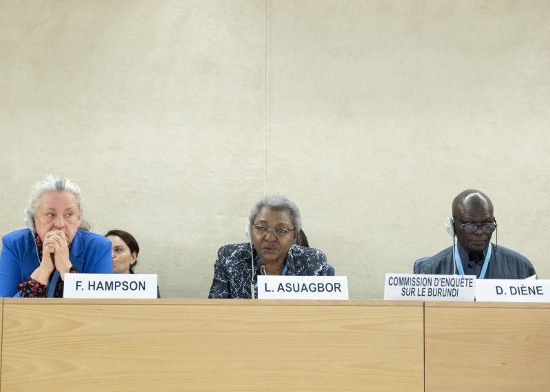 Les trois membres de la commission ont l'air pensif et préoccupé. Françoise Hampson est une femme blanche aux cheveux poivre et sel. Lucy Asuagborest une femme noire aux cheveux gris. Doudou Diene est un homme noir chauve, assez âgé.