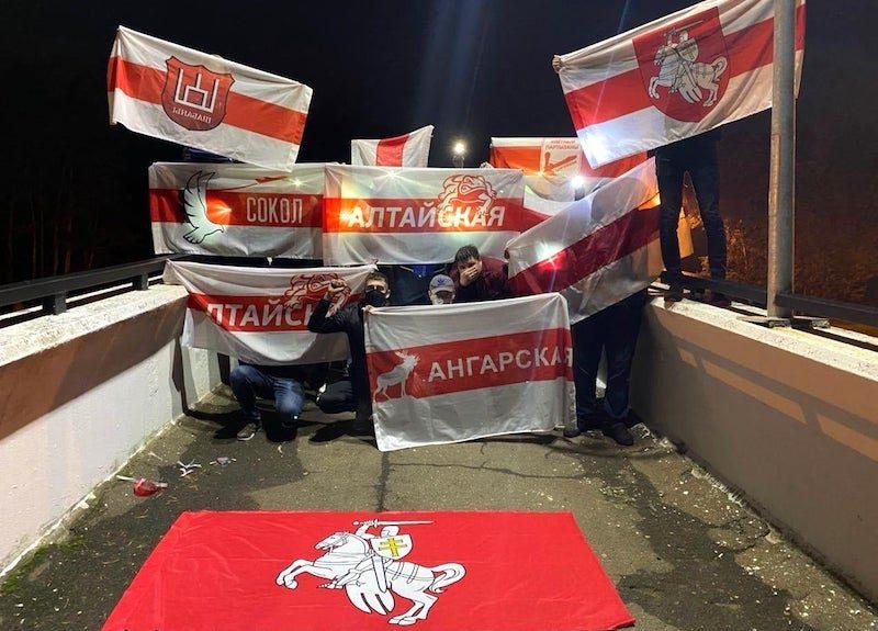 Plusieurs personnes posent avec des drapeaux rouge et blanc représentant divers quartiers de Minsk.