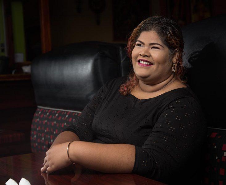 Portrait de l'humoriste Rhea-Simone Auguste, souriante dans une chemise noire. Elle est claire de peau, corpulente et arbore un  large sourire.