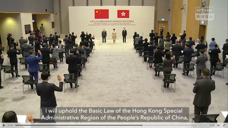 L'image montre une cérémonie de prestation de serment des fonctionnaires du gouvernement de la région administrative spéciale de Hong Kong (RASHK) à Hong Kong. Elle se tient dans une pièce plutôt large, éclairée avec un haut plafond. On distingue de nombreuses personnes, hommes et femmes, de dos, se tenir debout avec la main droite levée. Face à cette assemblée, il y a 3 personnes, 1 femme et 2 hommes : Carrie Lam, cheffe de l'exécutif de Hongkong accompagnée de hauts fonctionnaires. Derrière elles se trouve un panneau gigantesque avec le drapeau chinois et le drapeau hongkongais. En dessous, un texte est écrit en chinois et en anglais. Quelques caméras sont visibles. En haut, à droite figure le logo de RTHK (Radio Television Hong Kong). Au bas de l'image on lit, en grisé, une phrase en anglais : « I will uphold the Basic Law of the Hong Kong Special Administrative Region of the Peoples's Republic of China, » (« Je ferai respecter la loi fondamentale de la région administrative spéciale de Hong Kong de la République populaire de Chine »).