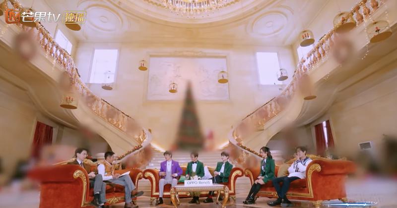L'image montre une grande pièce avec un haut plafond. Un grand escalier mange l'image et se sépare a l'étage sur la gauche et la droite. Au premier plan, 7 jeunes gens sont assis sur des canapés de style ancien, de couleur marron. Ils sont vêtus de vêtements d'époque. Sur l'image, on voit de nombreux plans floutés : un sapin de Noël, au milieu de l'image, et des décorations suspendues sur les deux côtés des escaliers. Le logo de la chaîne de télévision, « Mango TV », apparaît en haut à gauche, en caractères chinois.